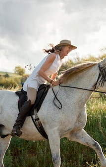 Side view of female farmer horseback riding outdoors in nature