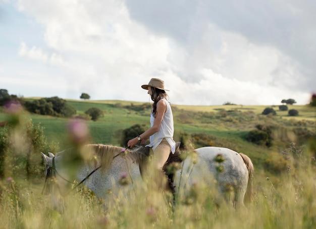 Side view of female farmer horseback riding
