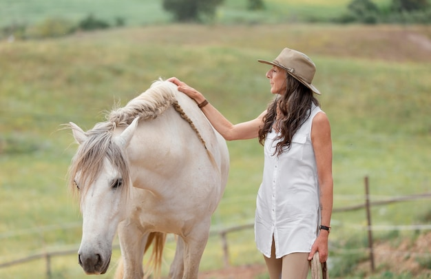 Side view of female farmer petting her horse