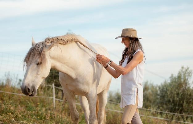Vista laterale del coltivatore femminile che tesse i capelli del suo cavallo