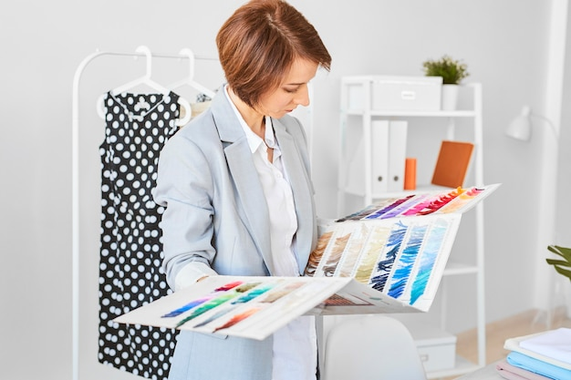 Side view of female fashion designer consulting color palette for clothing line