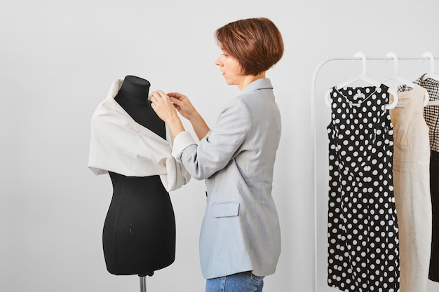 Side view of female fashion designer working in atelier with dress form
