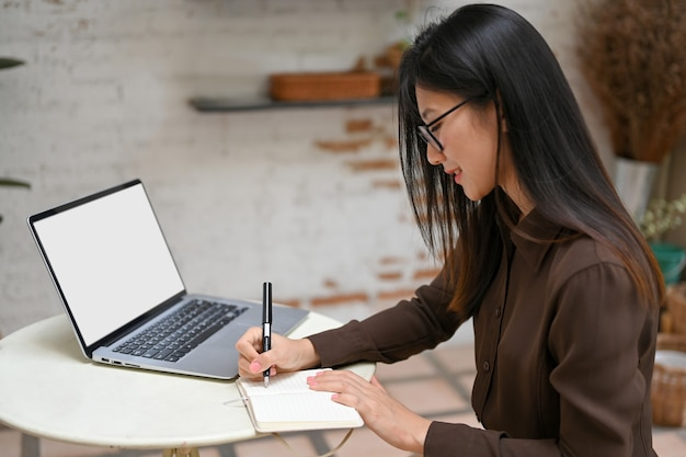 Side view of female freelancer hand writing on notebook while working with laptop on round table in cafe