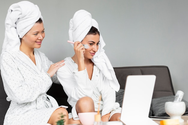 Side view of female friends indulging in skin care
