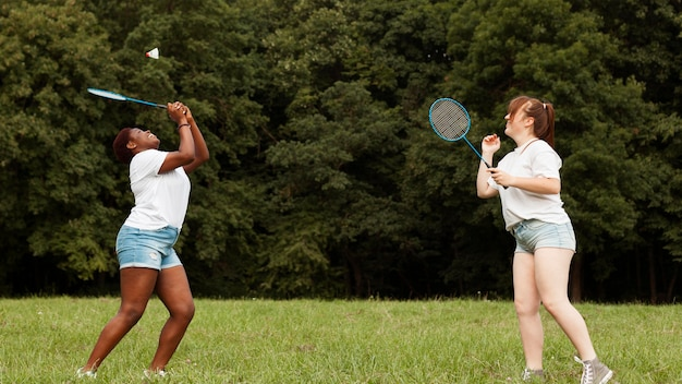 Side view of female friends playing badminton outdoors