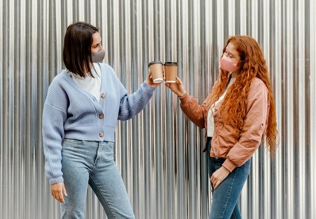 Vista laterale di amiche con maschere facciali all'aperto che incoraggiano con tazze di caffè