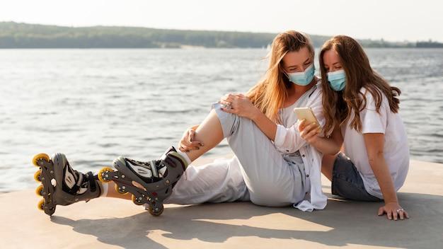 Vista laterale di amiche con maschere mediche e lame a rullo in riva al lago