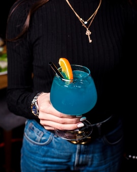 Side view of female hand holding a glass of blue lagoon cocktail decorated with orange slice on dark