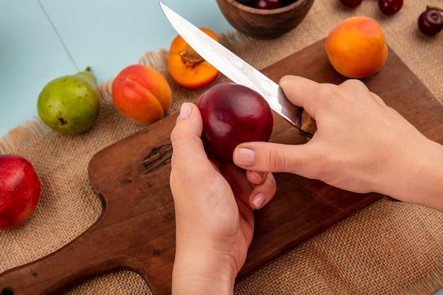 Vista laterale delle mani femminili che tagliano la pesca con il coltello e l'albicocca sul tagliere e le ciliegie nella ciotola albicocca della pera della pesca su tela di sacco e sfondo blu