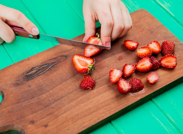 Side view of female hands cutting strawberries with knife on cutting board on green surface