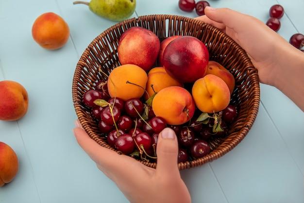 Vista laterale delle mani femminili che tengono cesto di frutta come albicocche e pesche con ciliegie pere su sfondo blu