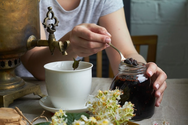 Side view of female hands puts homemade jam in cup of tea from samovar