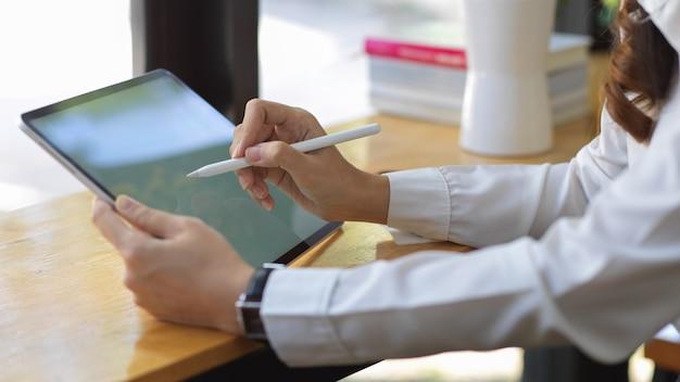 Side view of female hands using mock up digital tablet on wooden bar in cafe