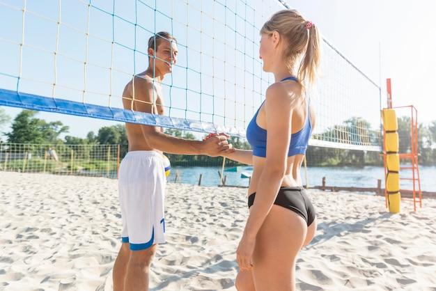 Vista laterale della mano di giocatori di pallavolo femminile e maschile tremare sotto la rete