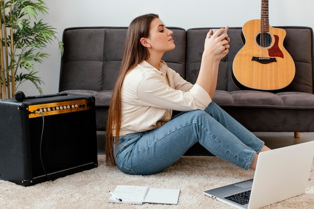 Side view of female musician holding mug next to acoustic guitar