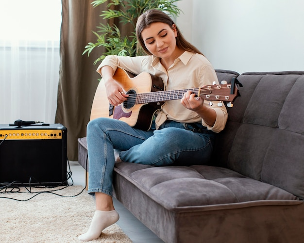 Side view of female musician at home playing acoustic guitar while sitting on the sofa