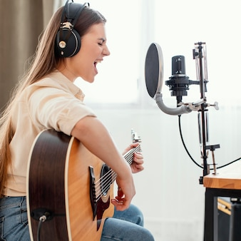 Side view of female musician at home recording song and playing acoustic guitar