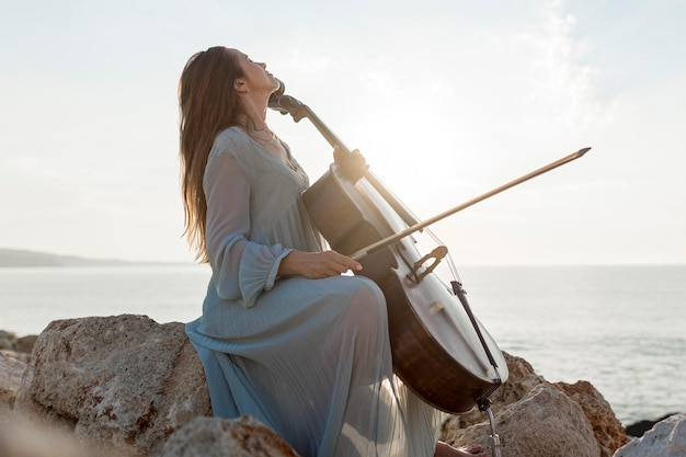 Side view of female musician playing cello by the sea