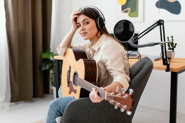 Side view of female musician posing with acoustic guitar at home