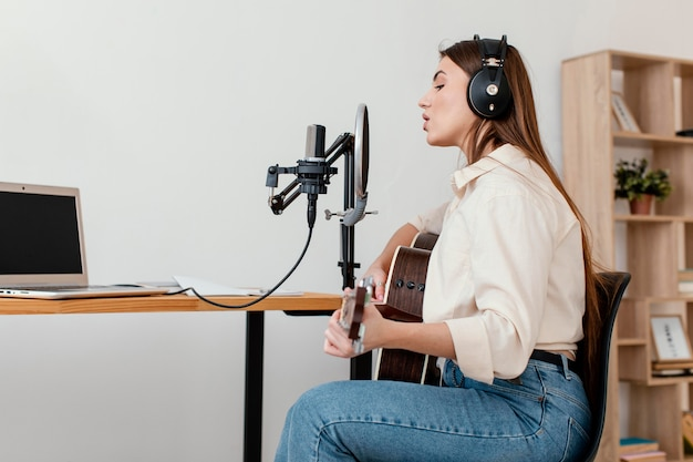 Side view of female musician recording song with microphone while playing acoustic guitar at home