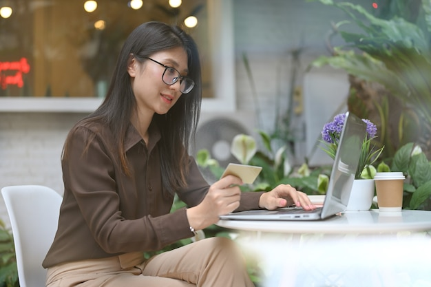 Side view of female office worker doing online banking on laptop while sitting in cafe