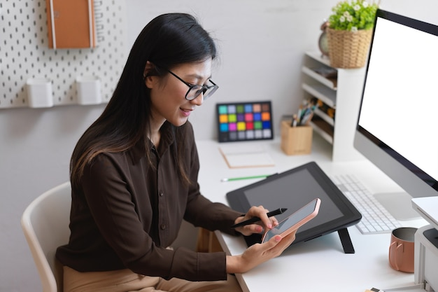 Side view of female office worker hand using smartphone while working with designer supplies