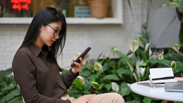 Side view of female office worker using smartphone while siting and waiting for coffee in coffee shop