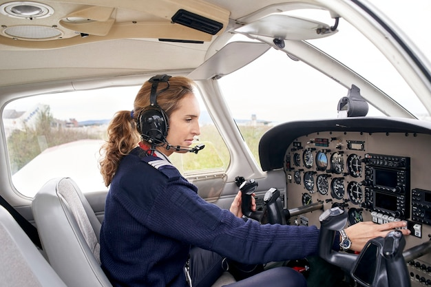 Side view of a female pilot in the cockpit of an airplane touching some buttons