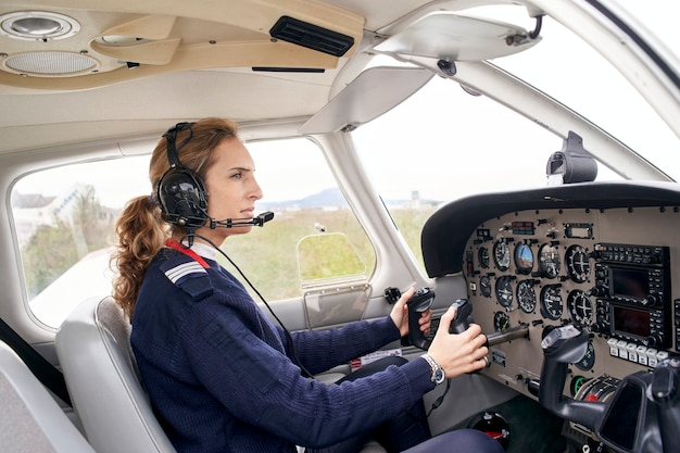 Side view of a female pilot in the cockpit of an airplane