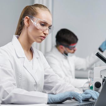 Vista laterale della ricercatrice in laboratorio con occhiali di sicurezza