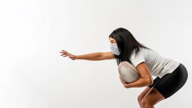 Vista laterale del giocatore di rugby femminile con palla e mascherina medica