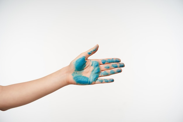 Side view of female's hand with blue colour on it being raised while going to shake somebody's hand, spreading it ahead while posing on white