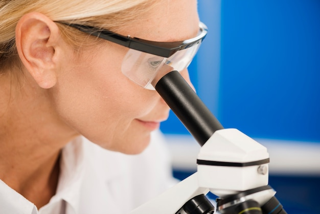 Vista laterale della scienziata che analizza facendo uso del microscopio in laboratorio