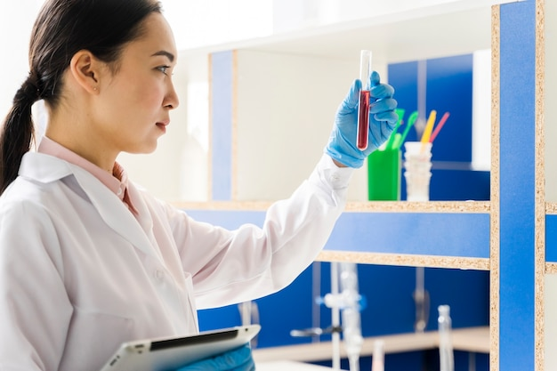 Side view of female scientist holding tablet and substance