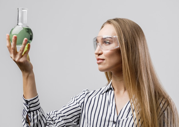 Side view of female scientist holding test tube while wearing safety glasses