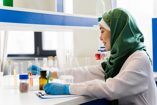 Side view of female scientist with hijab and surgical gloves