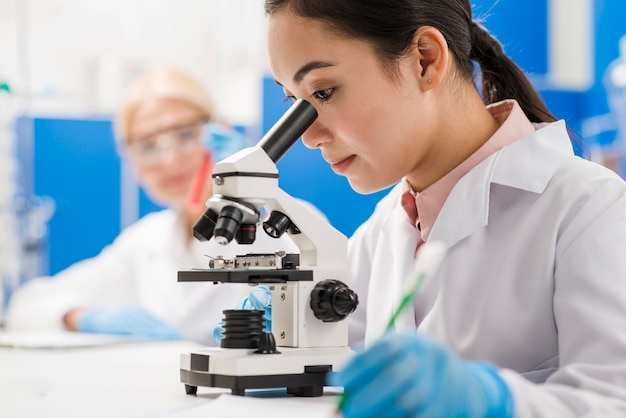 Side view of female scientist with microscope in the lab