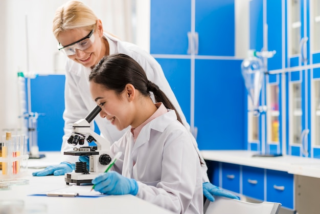 Side view of female scientists working at microscope in the lab
