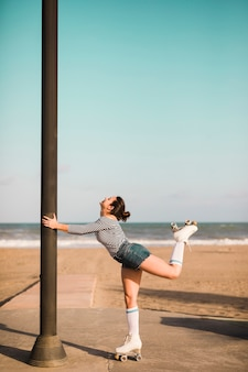 Side view of a female skater holding pillar standing in front of beach