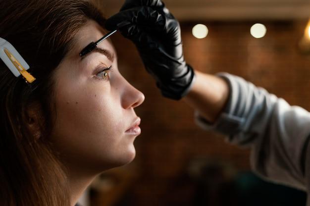 Vista laterale dello specialista femminile che fa un trattamento delle sopracciglia per la donna
