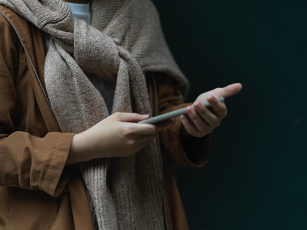 Side view of female in sweater using smartphone while standing in dark background