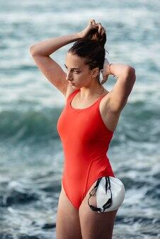 Vista laterale del nuotatore femminile che organizza i suoi capelli prima di nuotare