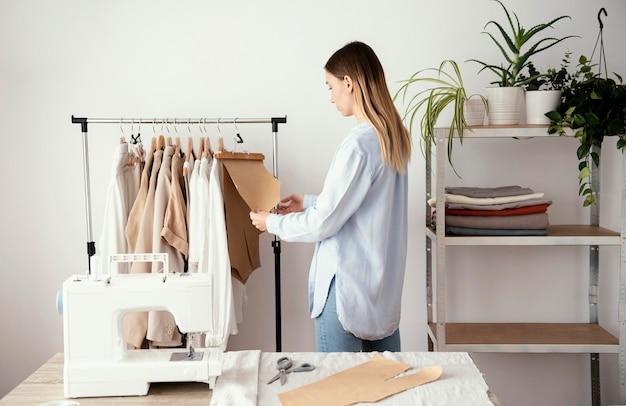 Vista laterale del sarto femminile che prepara tessuto per indumenti