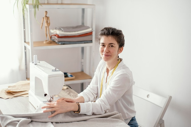 Side view of female tailor working in the studio with sewing machine