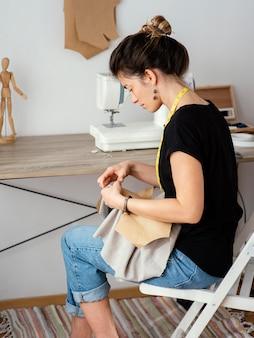 Vista laterale del sarto femminile che lavora in studio
