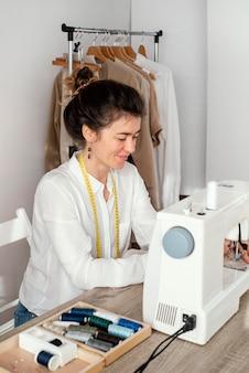 Vista laterale del sarto femminile che lavora con la macchina da cucire