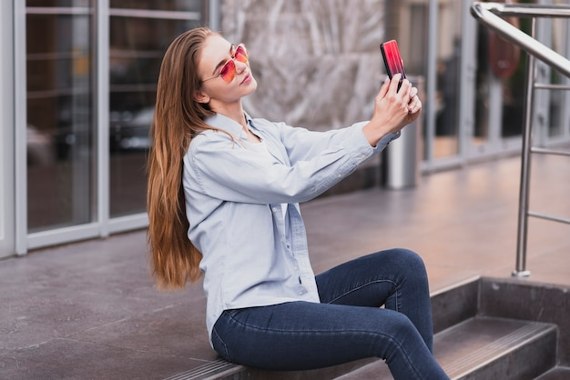 Side view female taking selfies