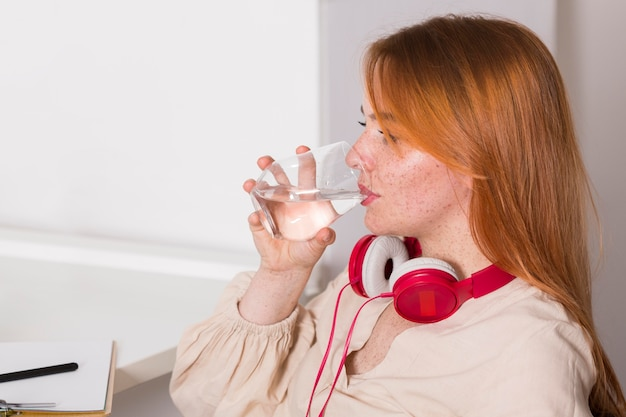 Side view of female teacher drinking water during online class