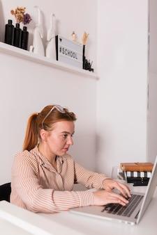 Vista laterale dell'insegnante femminile che utilizza computer portatile durante la lezione in linea
