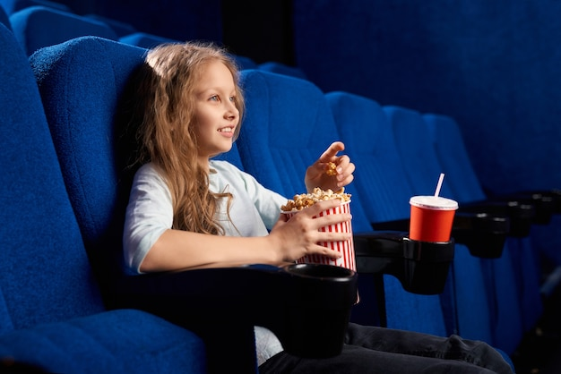Side view of female teen watching movie in empty cinema. little girl eating popcorn, having rest and relaxing in comfortable chair during weekend